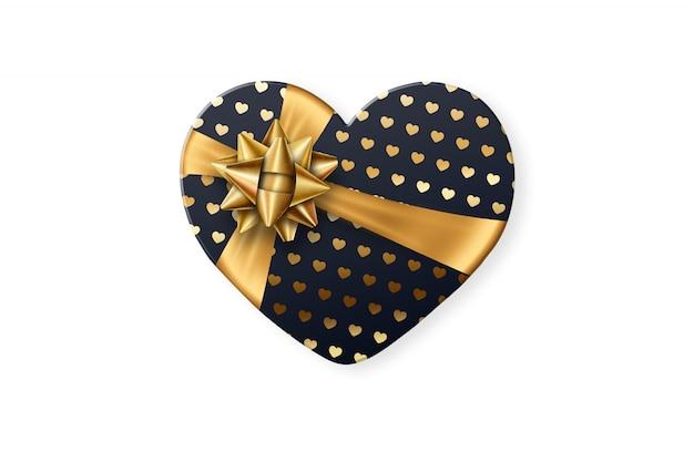 Schwarze geschenkbox in form eines herzens mit einem festlichen goldbogen lokalisiert auf weißem hintergrund
