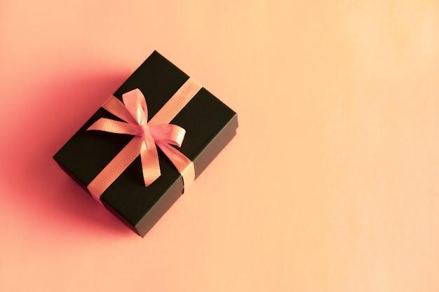 Schwarze geschenkbox mit orange bogen auf korallenrotem rosa pastellhintergrund. flach lag festlich minimaler stil.