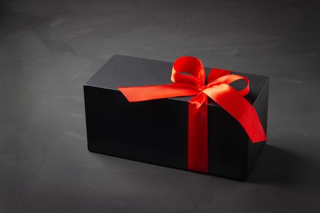 Schwarze geschenkbox mit rotem band auf dunklem hintergrund