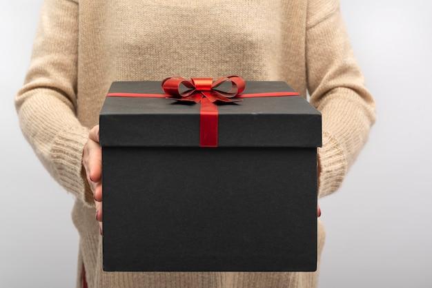 Schwarze geschenkbox mit roter schleife in weiblichen händen.