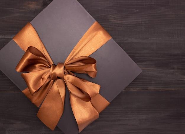 Schwarze geschenkbox mit satinband auf dem tisch