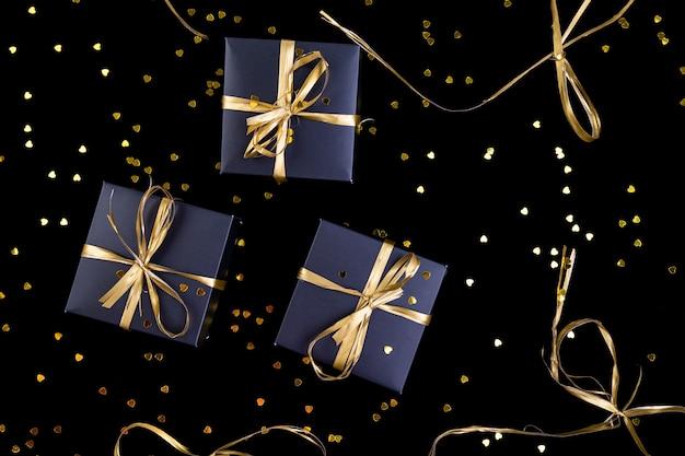 Schwarze geschenkboxen mit goldband auf glanz. flach liegen.