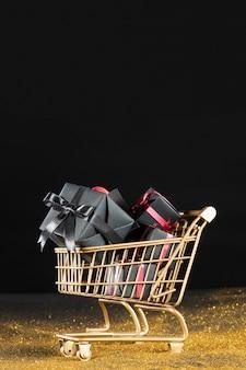 Schwarze geschenke im goldenen einkaufswagen