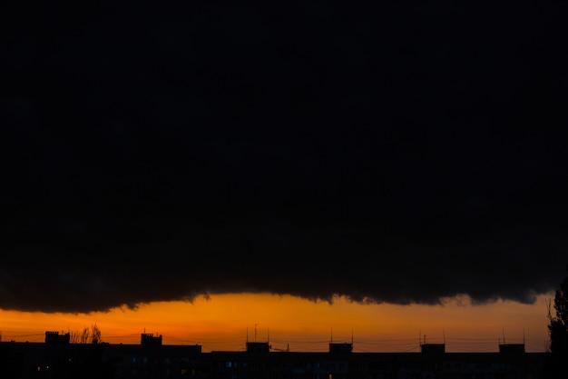 Schwarze gewitterwolken bei sonnenuntergang. leuchtend orange sonnenuntergang und dunkle wolken. sturmhimmel