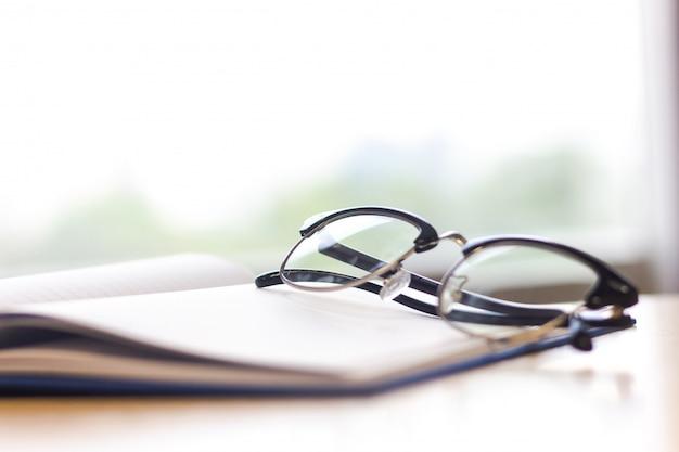 Schwarze gläser auf notizbuch auf tabelle. nahaufnahmegläser.