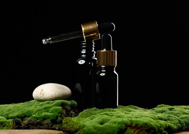 Schwarze glasflasche mit pipette steht auf grünem moos, schwarzer hintergrund. kosmetik spa-branding. verpackungen für gel, serum, werbung und produktwerbung, mock-up