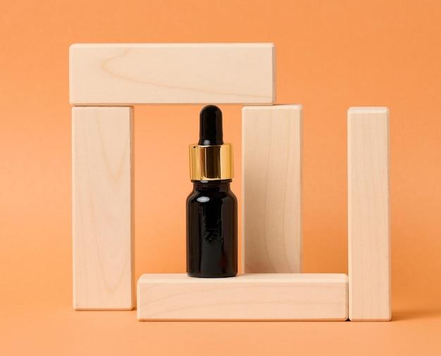 Schwarze glasflasche mit tropfer für kosmetika auf orangefarbenem hintergrund. verpackungen für gel, serum, werbung und verkaufsförderung. natürliche bio-produkte. attrappe, lehrmodell, simulation