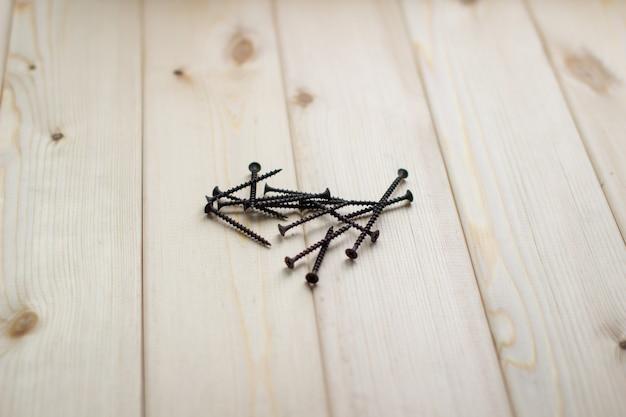 Schwarze große schrauben oder selbstschneidende schrauben aus hochfestem stahl für holzprodukte liegen auf einem hölzernen hintergrund.