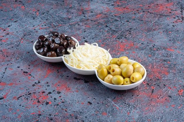Schwarze, grün marinierte oliven und weißkäse in weißen tassen.
