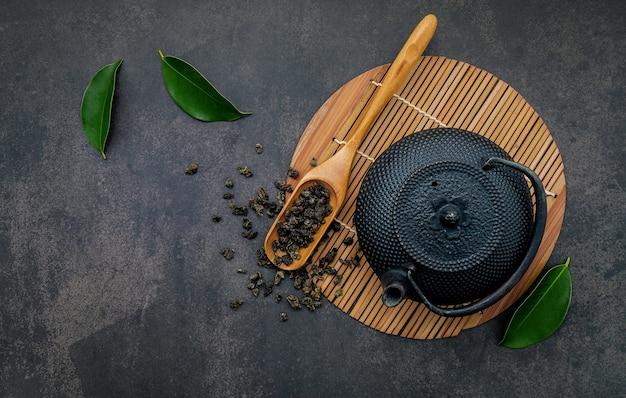 Schwarze gusseisen-teekanne mit kräutertee auf dunklem stein.