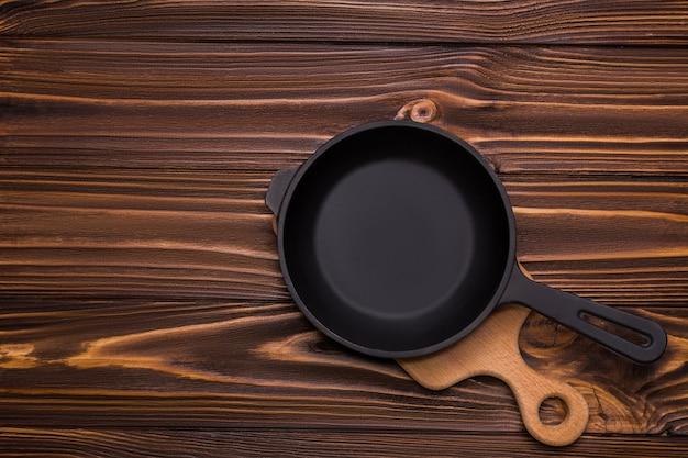 Schwarze gusseiserne leere bratpfanne auf einem hölzernen hintergrund. kochgeschirransicht von oben