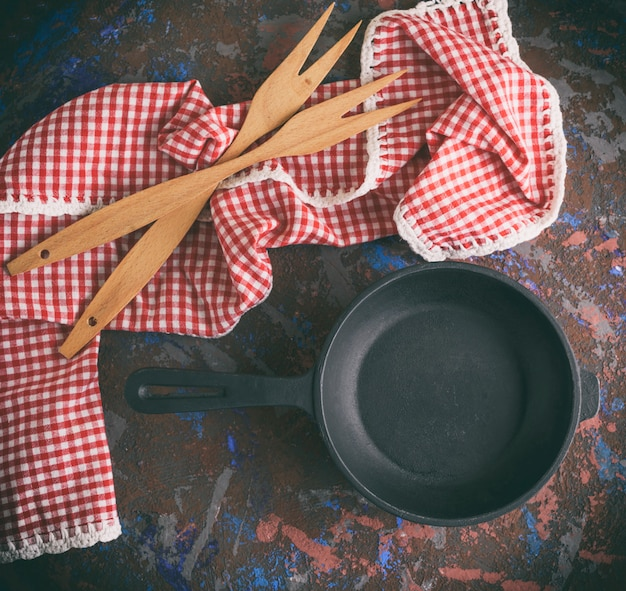 Schwarze gusseiserne pfanne mit griff und zwei holzgabeln