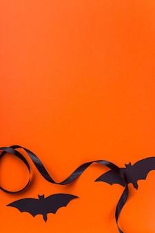 Schwarze halloween-charaktere und -zubehör auf einer hellen orange oberfläche