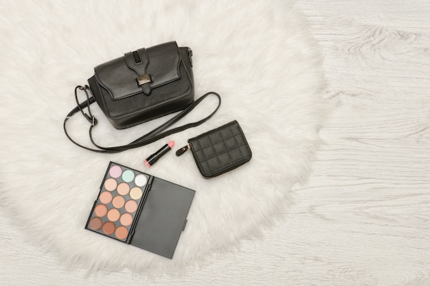 Schwarze handtasche, lidschatten, brieftasche und lippenstift. weißes fell, ansicht von oben. modisches konzept