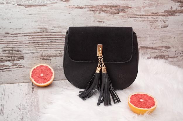 Schwarze handtasche mit pinseln auf weißem fell, eine halbe grapefruit, eine helle holzoberfläche
