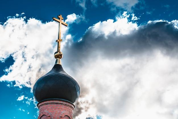 Schwarze haube der kirche mit einem goldenen kreuz auf dem himmelhintergrund mit weißen wolken. turm des alten roten backsteins angesichts der sonne