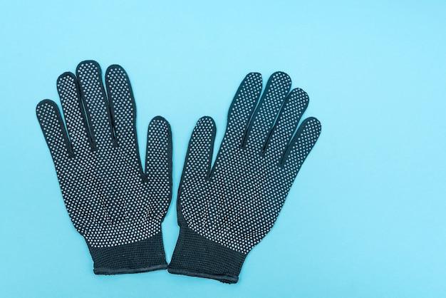 Schwarze haushalts- und medizinische handschuhe zum schutz auf blauem hintergrund.