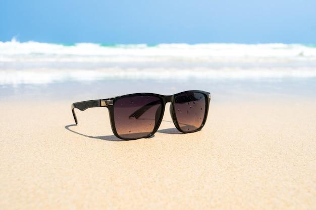 Schwarze herrensonnenbrille am strand. schöne tapete mit meerblick, hintergrund