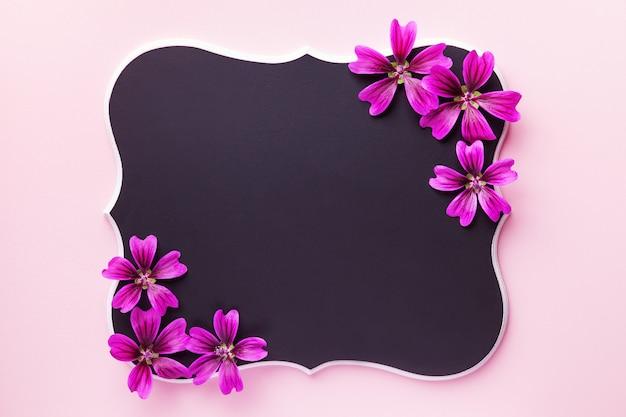 Schwarze hölzerne tafel mit purpurroten blumen