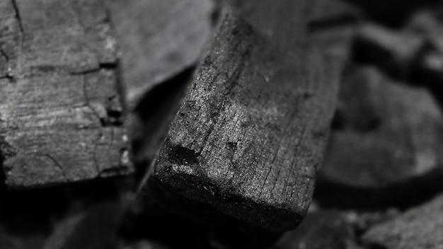 Schwarze holzkohle auf schwarzem strukturiertem boden holzkohle schwarzer kohlenstoff rückstände durch starkes erhitzen