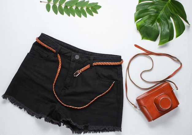 Schwarze jeansshorts mit ledergürtel, retro-kamera im cover auf weißem hintergrund mit grünen tropischen blättern.