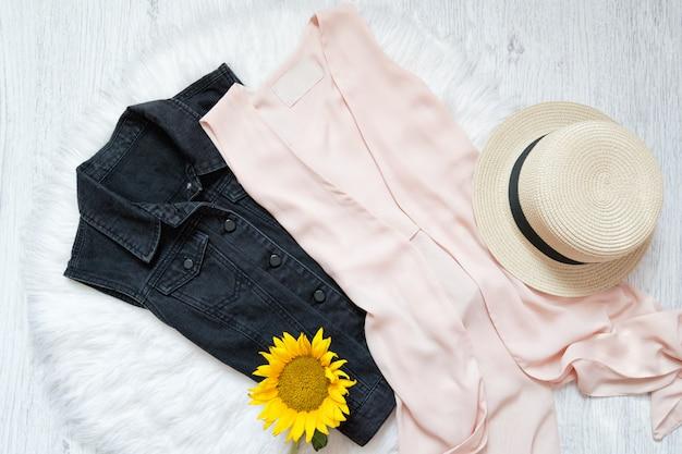 Schwarze jeansweste, chiffonumhang, hut und sonnenblume auf weißem fell
