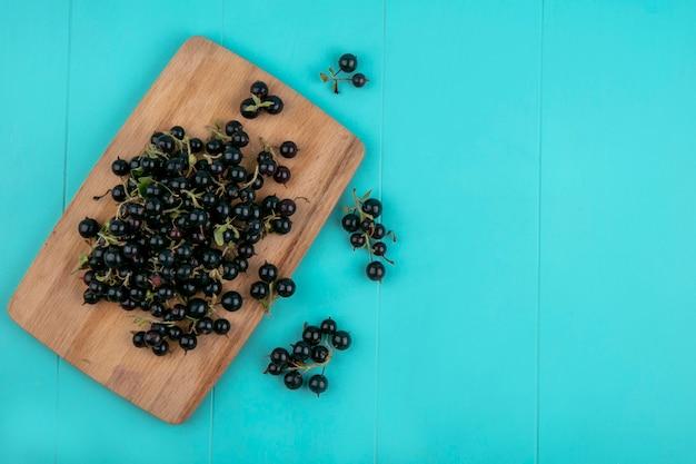Schwarze johannisbeere des kopierraums der draufsicht auf der tafel auf hellblauem hintergrund