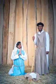 Schwarze jungfrau maria und schwarzer joseph in einer krippe