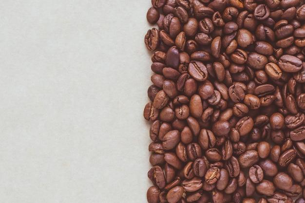 Schwarze kaffeebohnen auf papierhintergrund mit copyspace.