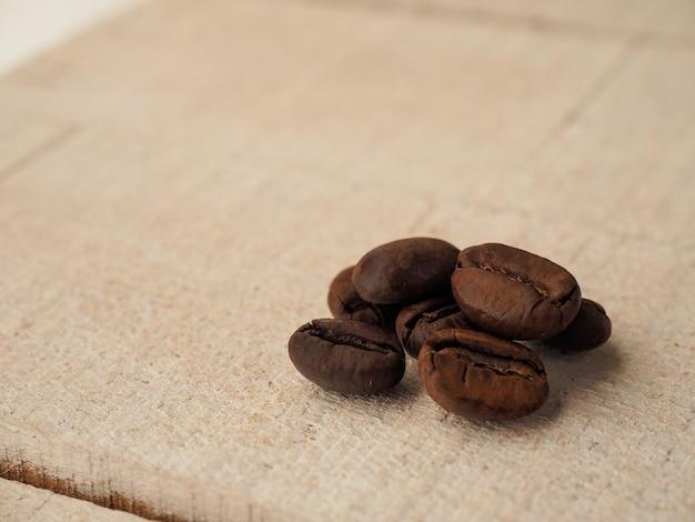 Schwarze kaffeekörner liegen auf hellem holztisch, hintergrundbild. platz für text