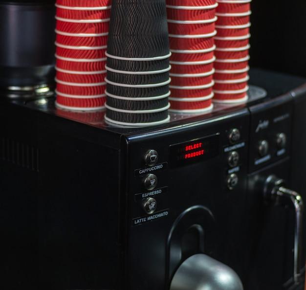 Schwarze kaffeemaschine, kaffeemaschine, kaffeemaschine mit pappbechern in den farben schwarz und rot