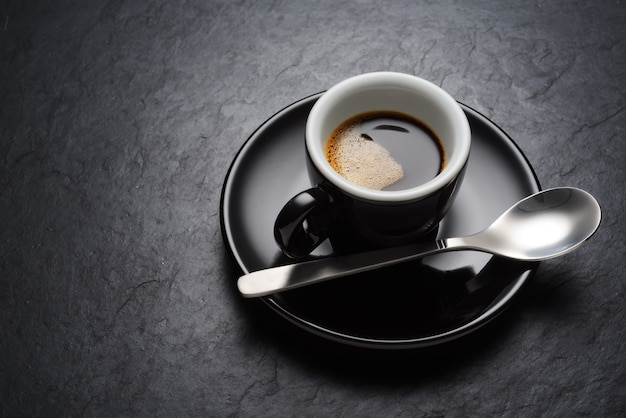Schwarze kaffeetasse auf der dunklen schieferhintergrundbeschaffenheit
