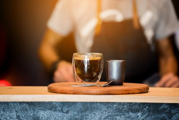 Schwarze kaffeetasse auf holztisch und kaffee-barista. filmeffekt.