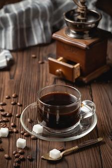 Schwarze kaffeetasse auf holztisch.