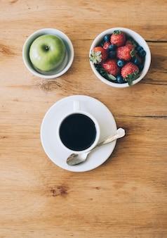 Schwarze kaffeetasse; grüner apfel; erdbeeren und blaubeeren in der schüssel auf holzoberfläche