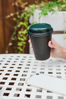 Schwarze kaffeetasse in der hand einer frau