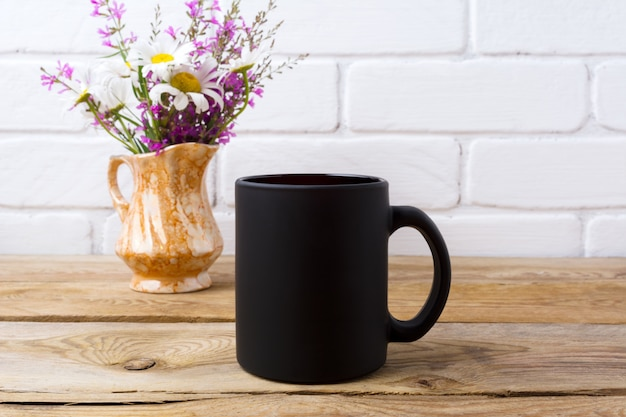 Schwarze kaffeetasse mit kamille und lila blumen im goldenen krug