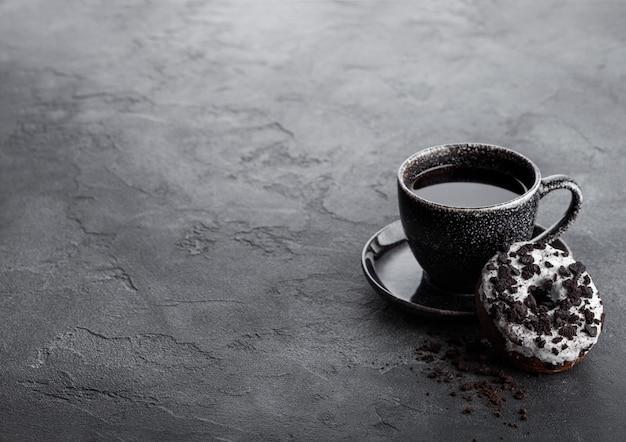 Schwarze kaffeetasse mit untertasse und donut mit schwarzen keksen auf schwarzem steinküchentisch.