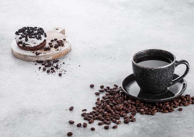 Schwarze kaffeetasse mit untertasse und donut mit schwarzen keksen auf steinküchentisch.