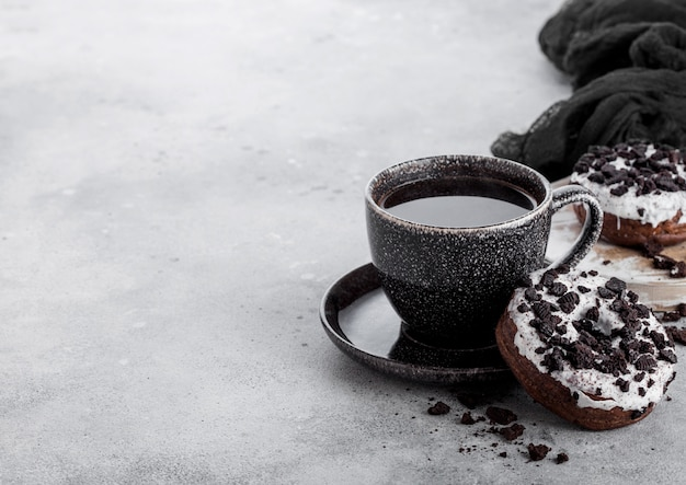 Schwarze kaffeetasse mit untertasse und donuts mit schwarzen keksen auf steinküchentisch.