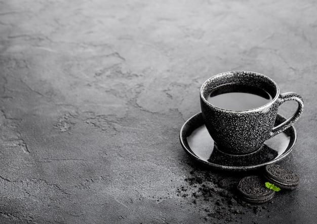 Schwarze kaffeetasse mit untertasse und schwarzen sandwichkeksen auf schwarzem steinküchentisch. frühstückssnack