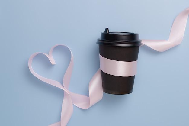 Schwarze kaffeetasse papier und rosa band in der form eines herzens auf einem blauen hintergrund. valentinstag konzept.