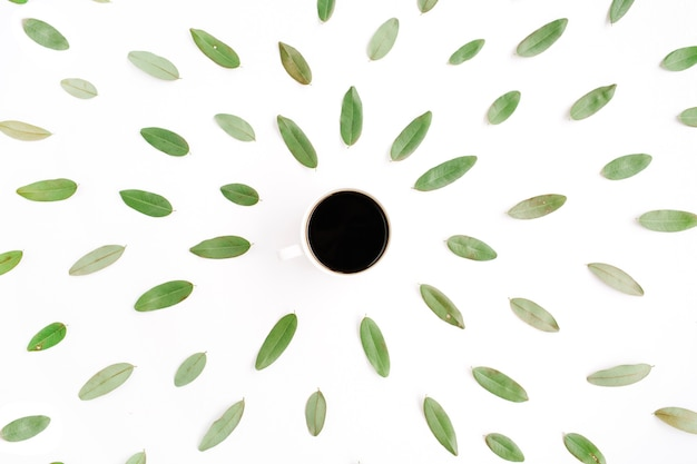 Schwarze kaffeetasse und blumenmuster mit grünen blütenblättern.