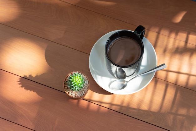 Schwarze kaffeetasse und kaktus auf hölzernem licht