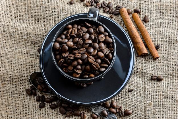 Schwarze kaffeetasse voller bio-kaffeebohnen und zimtstangen auf leinentuch