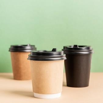 Schwarze kaffeetassen aus papier zum mitnehmen verspotten den grünen und braunen hintergrund