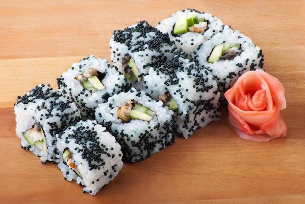Schwarze kalifornische sushi-rollen auf holzteller
