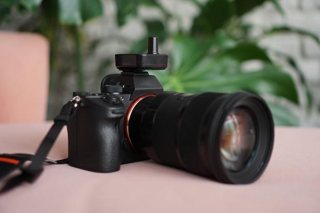 Schwarze kamera mit einem objektiv auf einem rosa hintergrund und einem unscharfen hintergrund von grünen blättern
