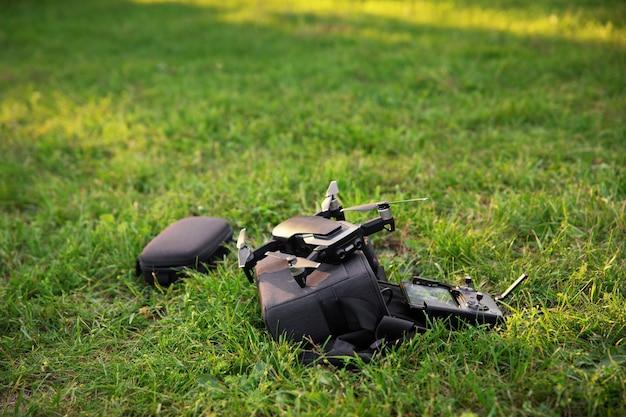 Schwarze kameradrohne mit fernbedienung und telefon als bildschirm bleibt auf dem grünen rasen, technologiekonzept