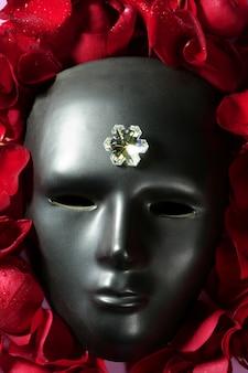 Schwarze karnevalsmaske mit roten rosenblättern